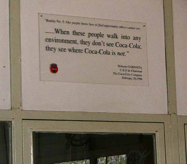 Coca-cola plaque being pretty honest about world domination